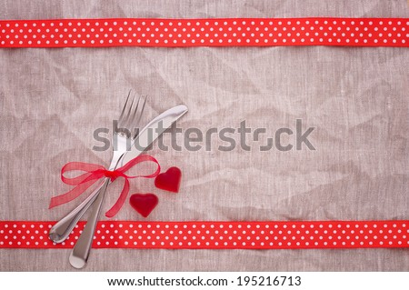 Cutlery for celebratory dinner on Valentine's Day on napkin. Design for greeting card hearts red ribbon. Product pages for installation recipe books menu