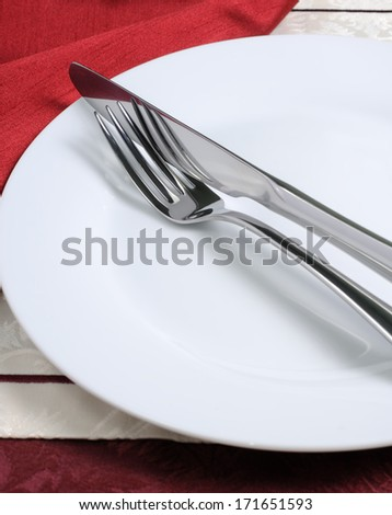 Cutlery (knife and fork) on a white plate with a napkin