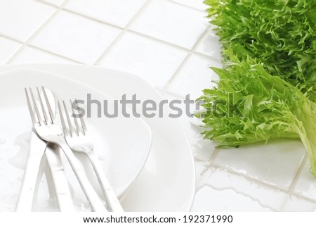 Cutlery on a plate beside a bunch of lettuce. - stock photo