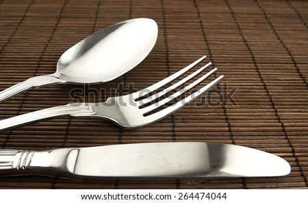 Cutlery on a wooden background. Fork, knife and spoon on brown table. - stock photo
