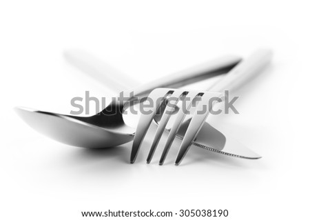 Cutlery set: fork, spoon and knife isolated on white background. Soft focus, shallow DOF. - stock photo