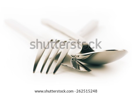 Cutlery set: fork, spoon and knife isolated on white background. Soft focus, shallow DOF. Toned image. - stock photo