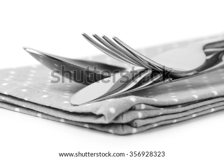 Cutlery set: spoon, fork and knife on napkin close-up. Monochrome black and white image.