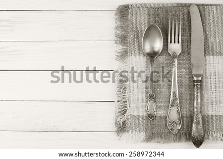 Cutlery set: vintage knife, fork and spoon on white wooden background. Toned image, sepia. - stock photo