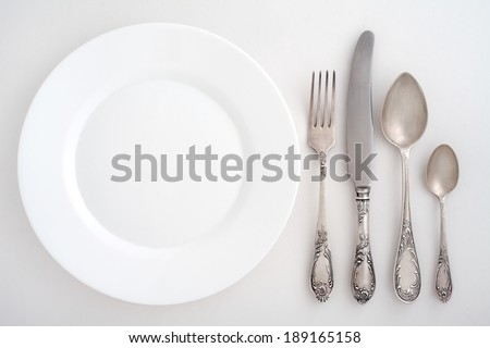 Cutlery set with fork, knife, spoon and plate. Overhead view. - stock photo
