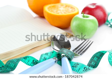 Cutlery tied with measuring tape and book with fruit close up