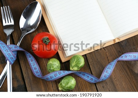Cutlery tied with measuring tape and book with vegetables on wooden background - stock photo