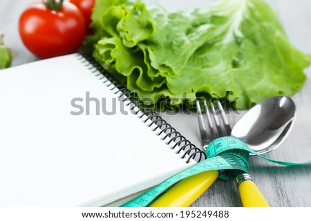 Cutlery tied with measuring tape and notebook with vegetables on wooden background - stock photo