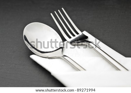 cutlery with napkin on a slate plate