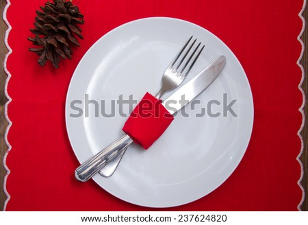 Cutlery wrapped with napkin on plate with Christmas decorations