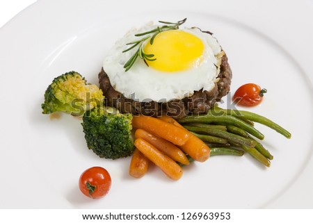 Cutlets,meat dish of minced meat in the form of bread with vegetables and fried eggs on a white plate