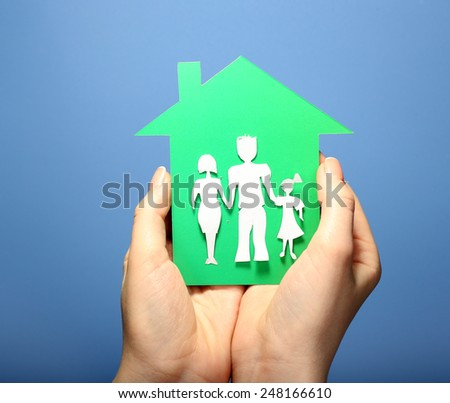 Cutout house with paper family in female hands on colorful background - stock photo