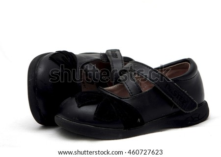 Cutout of a pair of black children's shoes on white background