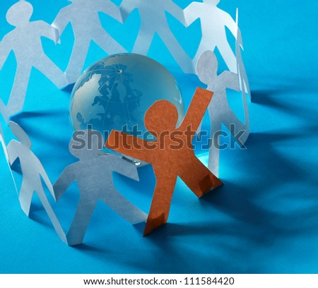 Cutout paper people standing around globe - stock photo