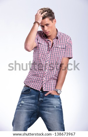 cutout picture of a casual young man adjusting his hair and holding his hand in his pocket while looking at the camera. on gray background