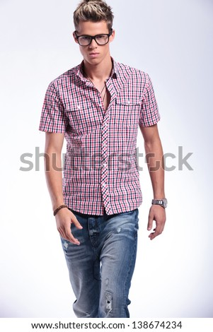 cutout picture of a casual young man walking and looking in the camera's direction with a serious expression. on gray background