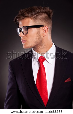 cutout portrait of a young business man looking sideways, against a dark background - stock photo