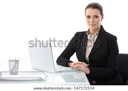 Cutout portrait of businesswoman sitting at desk with laptop computer, smiling at camera. - stock photo