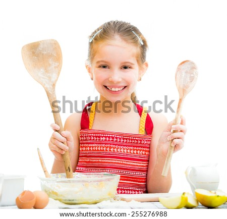 cutre little girl making dough shows wooden spoons isolated on a white background - stock photo