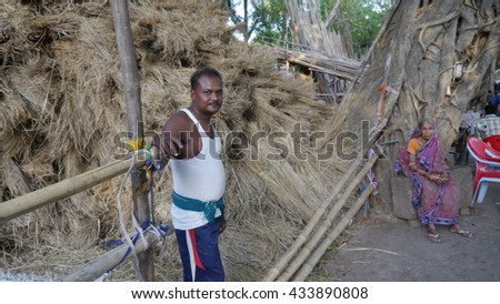 CUTTACK, INDIA - 17 MAY, 2016: An unidentified poor indian man standing near dried grass shop.