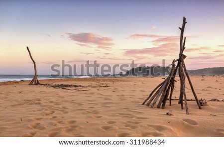 Cuttagee Beach in rural south coast NSW at dusk with tee pee made from random branches on the beach in foreground and Barraga rock in distance.. - stock photo