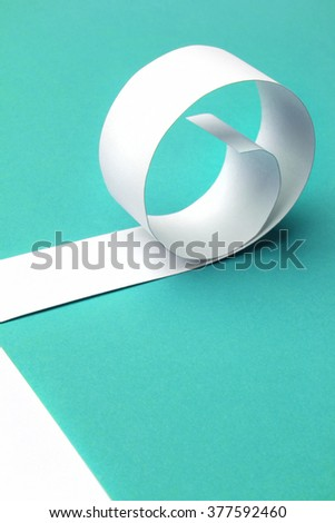 Cutted and rolled white paper with blue background - stock photo