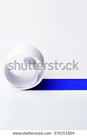 Cutted and rolled white paper with blue space for text - stock photo