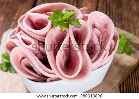 Cutted Ham Sausage on wooden background (selective focus) - stock photo