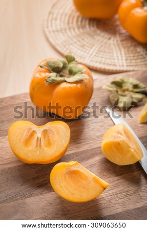 Cutted of Persimmon fruit on wood cutting board. - stock photo