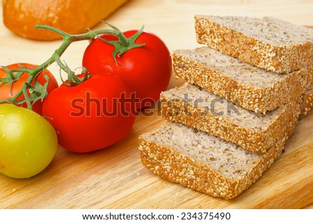 Cutted rye bread slices with seedsand tomatoes on a wooden board