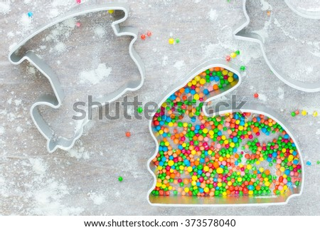 Cutter for the easter gingerbread shaped rabbit filled with colored sugar confectionery sprinkling on a white table. Preparation Easter cookies - stock photo