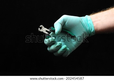 Cutter Pliers and a Hand on a Black Background