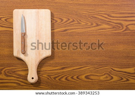 Cutting board and a kitchen knife on old wooden background. Top view