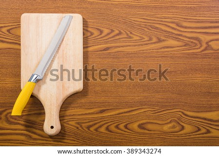Cutting board and a kitchen knife on old wooden background. Top view - stock photo