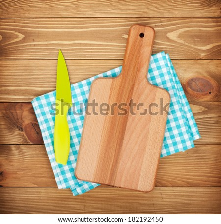 Cutting board and knife over kitchen towel on wooden table background - stock photo