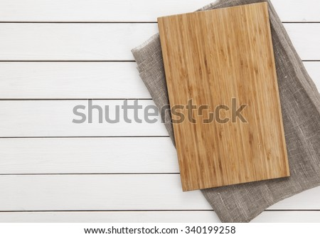 Cutting board and napkin on the wooden background. Top view. - stock photo