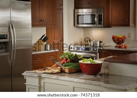 Cutting board and salad fixings on an island in a modern cherry kitchen - stock photo