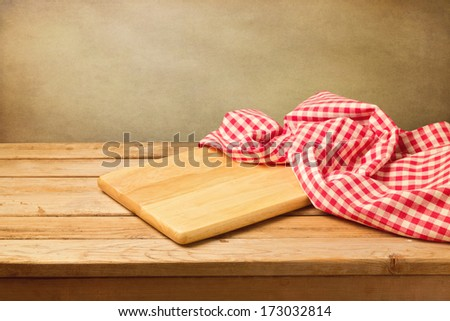 Cutting board and tablecloth on wooden table - stock photo
