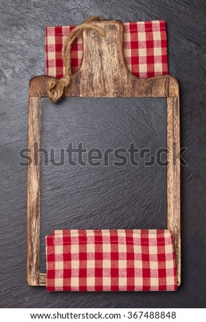 Cutting board and  tablecloth over dark slate board. - stock photo