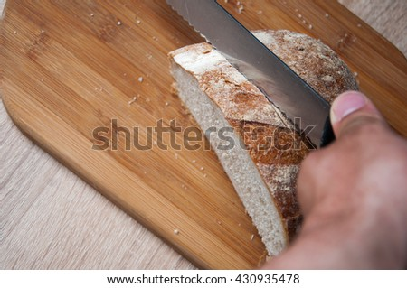 Cutting board, bread and a knife lying on a wooden table