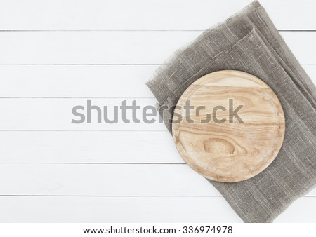 Cutting board on vintage wooden background. Round cutting board on white wooden table - stock photo