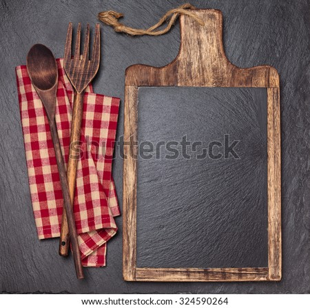 Cutting board, tablecloth, wooden spoons and piece of chalk. Over dark slate board. - stock photo