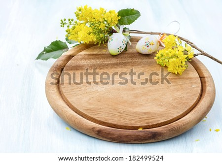 Cutting board with a blossoming branch and easter eggs. - stock photo