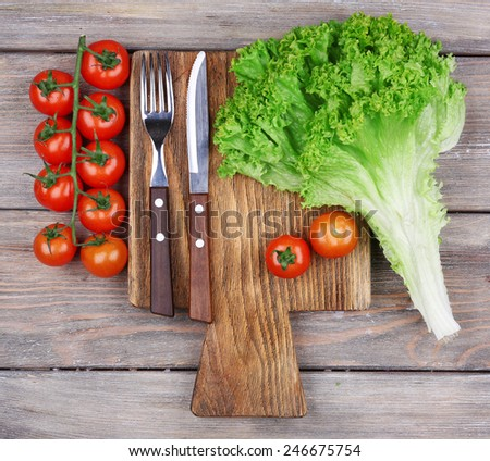 Cutting board with cherry tomatoes and lettuce on rustic wooden planks background - stock photo