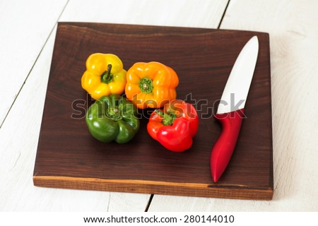 Cutting board with colorful sweet peppers - stock photo