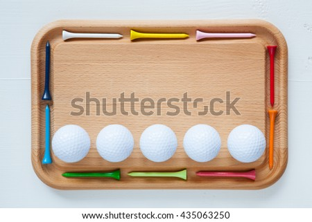 Cutting board with different wooden golf tees and golf balls - stock photo