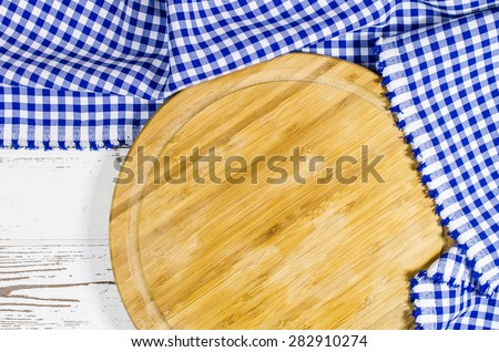 Cutting board with folded tablecloth on white wooden table