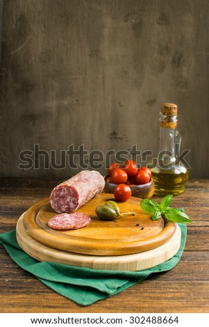 cutting board with Italian antipasti on a wooden table