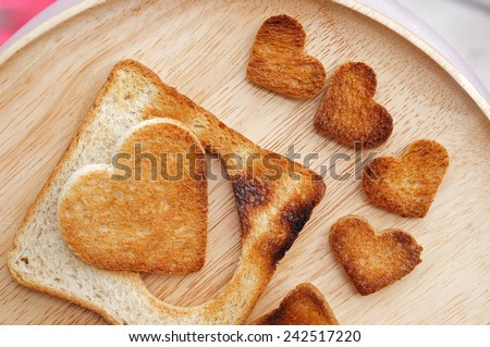 Cutting bread in shape of heart on the spoon. Concept about love and relationship.           - stock photo