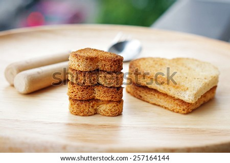 Cutting bread in shape of heart on wooden dish. Concept about love and relationship.